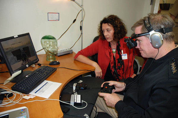 A psychologist of the Virtual Reality Research Program guides an officer through a demonstration of a virtual realty post-traumatic stress disorder treatment software program at Naval Medical Center in San Diego.